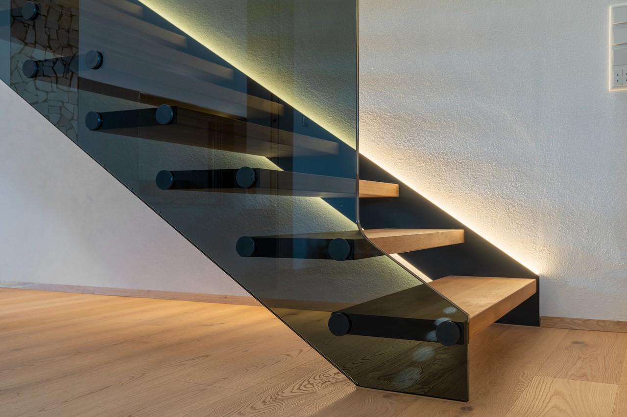 Holzstiege mit dunklem Glasgeländer